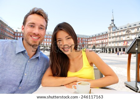 Madrid tourists taking selfie picture at cafe drinking coffee having fun on Plaza Mayor. Portrait of tourist couple sightseeing visiting tourism landmarks and attractions in Spain. Young woman and man - stock photo