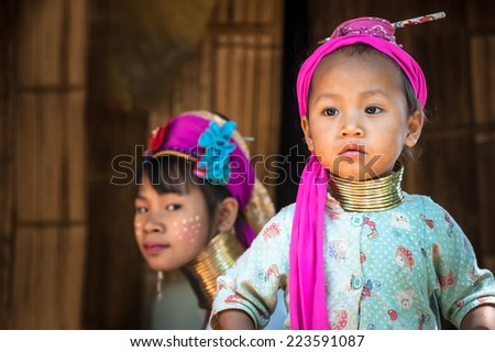MAE HONG SON, THAILAND - DEC 4, 2013: Unidentified Karen (Kayan Lahwi Padaung) Long Neck girl and young woman with traditional brass coils and clothes in tribe village. Chang Rai province, Thailand  - stock photo