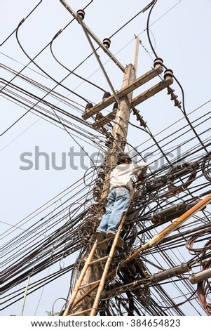MAE SOT, TAK, THAILAND - MARCH 02, 2016 : Technician is wiring the additional fiber optic cable access to the chaos of cables at Mae Sot, Tak, Thailand. - stock photo