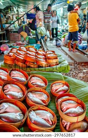 MAEKLONG, AUG 25: Train passing through the famous open air railway markets at Maeklong. Three times a day the train runs through these stalls  on August 25, 2008. Samutsongkram Province, Thailand - stock photo