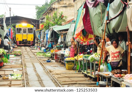 MAEKLONG, THAILAND-AUG.20: The famous railway markets at Maeklong, Thailand, August 20 th, 2012, Bangkok, Thailand.Three times a day the train runs through these stalls. - stock photo