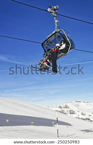 MAENNLICHEN, SWITZERLAND - DECEMBER 31, 2013: Family on ski and snowboards in the cable car cabin in winter swiss alps - stock photo