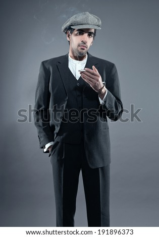 Mafia fashion man wearing grey striped suit with cap. Smoking cigarette. Black hair and brown skin. Studio shot. - stock photo