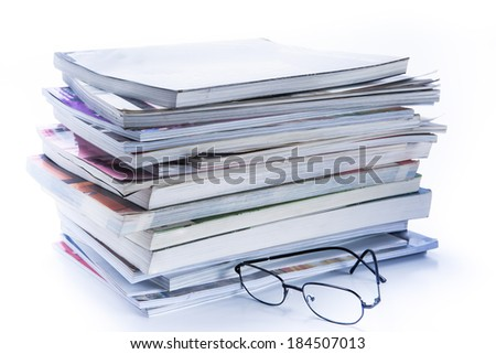 magazine and book stack with glasses - stock photo