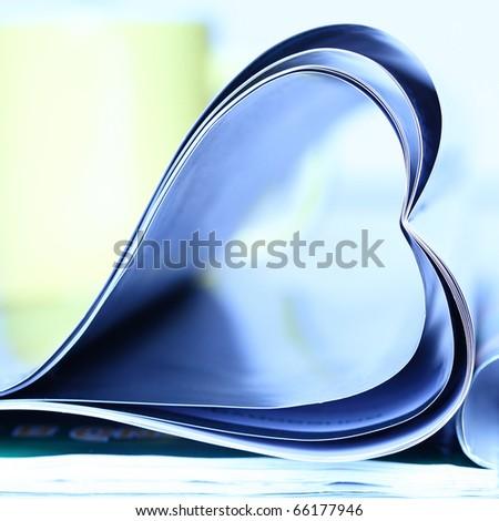 Magazine folded to heart shape over white background - stock photo
