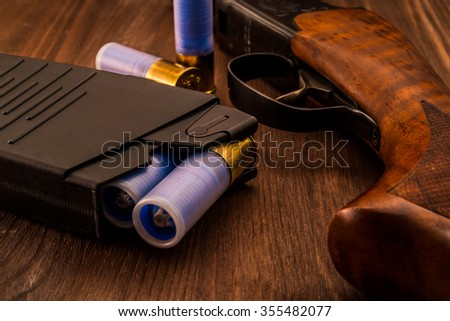 Magazine with bullet cartridges 12 gauge and shotgun on the wooden table. Close up view - stock photo