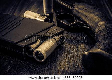 Magazine with bullet cartridges 12 gauge and shotgun on the wooden table. Close up view, image vignetting and the yellow toning - stock photo