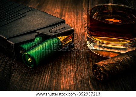 Magazine with cartridges 12 gauge and glass of whiskey and cuban cigar on the wooden table. Close up view, image vignetting and the orange-blue toning - stock photo