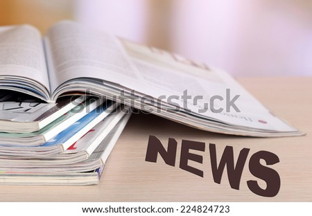 Magazines on wooden table, bright background - stock photo