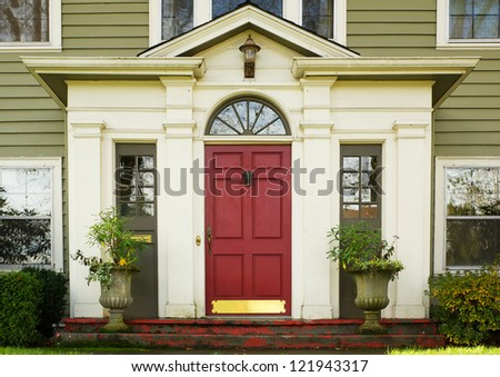 Magenta Home door bordered by two large potted plants - stock photo