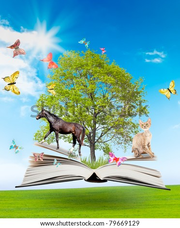 Magic book with a green tree and diferent animals on the background of nature. Symbol of knowledge. - stock photo