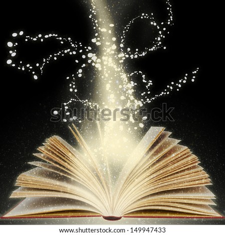 Magic book with bright light coming from its open pages - stock photo
