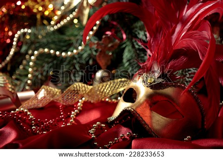 magic Christmas background with golden carnival  mask on  red silk  fabric  - stock photo