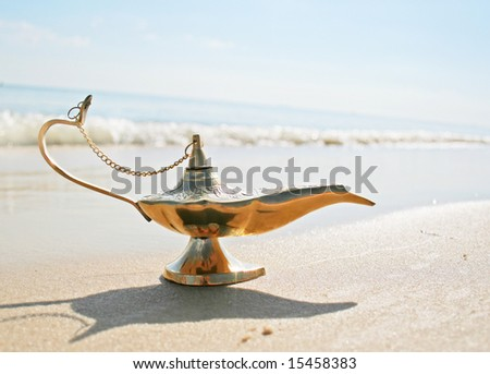 Magic Genies lamp on seashore - stock photo