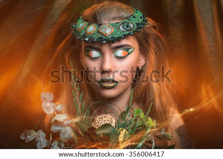 Magic golden girl with bright makeup. Streams of gold shiny drops on the background, cosmetics paint for body art. Big lips green shadows on eyes decorations accessories. Professional photo new idea - stock photo