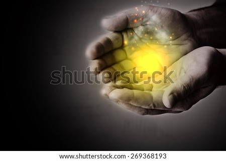 Magic in open palms. Image with toning and  light effects - stock photo