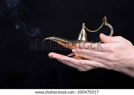 Magic lamp in female hands isolated on black - stock photo