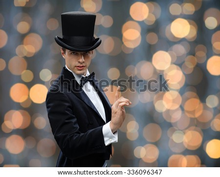 magic, performance, circus, show concept - magician in top hat pointing finger up over nigh lights background - stock photo