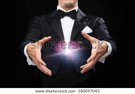 magic, performance, circus, show concept - magician in top hat showing trick - stock photo