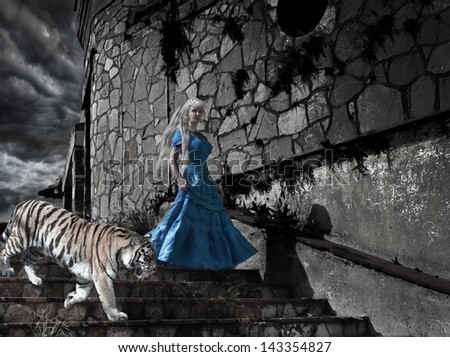 Magic scene- fantastic princess from fairy tale with a tiger on old tower steps - stock photo