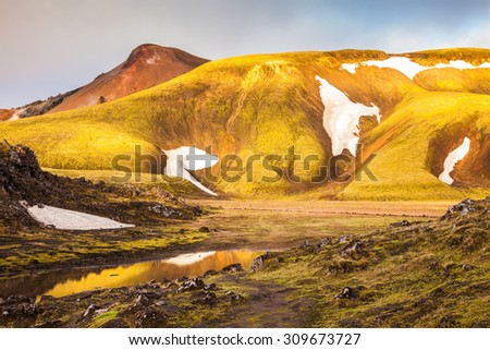 Magic sunrise in the Arctic. The golden light of dawn illuminates the mountains and glaciers national park Landmannalaugar, Iceland - stock photo
