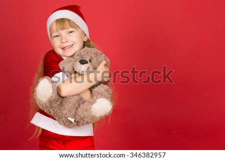 Magic winter. Horizontal portrait of a beautiful little girl laughing happily hugging her teddy bear - stock photo