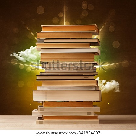 Magical books with ray of lights and colorful clouds on vintage background - stock photo