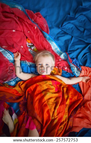 Magical cute blond Caucasian baby girl in skirt laying on a blue bed sheet covered with beautiful red, yellow, orange shawl cover. Concept childhood, happiness, fairy tale. View from above. Studio.  - stock photo