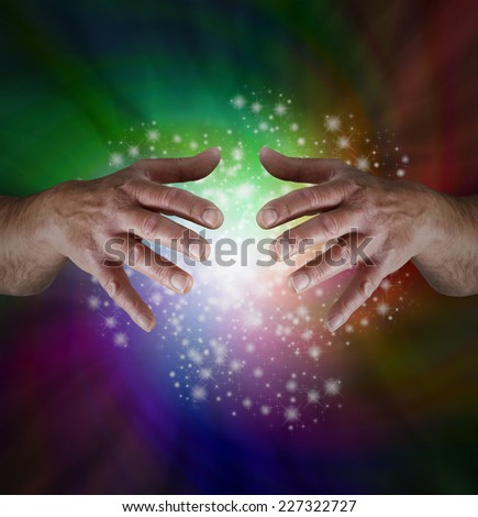 Magical Rainbow Sparkles   -   Male hands emerging from spiraling color background with white light and sparkles between - stock photo