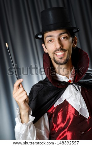 Magician in the dark room with wand - stock photo
