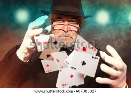 Magician show with playing cards. On color background - stock photo