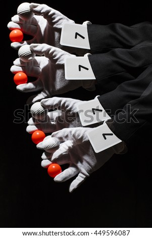 Magician waving his hand. In hand he has a red and white ball. Sleeve is a playing card with the number seven. Photo taken with a long exposure time and used stroboscopic flash. Includes a effect. - stock photo