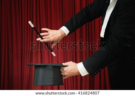 Magician with magic wand and top hat, performing on stage. Low key - stock photo