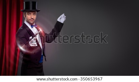 Magician with  magic wand in action  - stock photo
