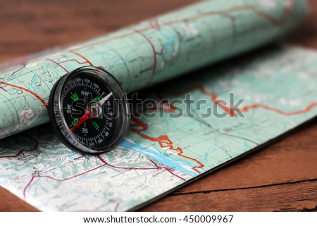 Magnetic compass on a topographic map. - stock photo