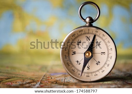 Magnetic compass standing upright on a world map conceptual of global travel , tourism and exploration, with copyspace - stock photo