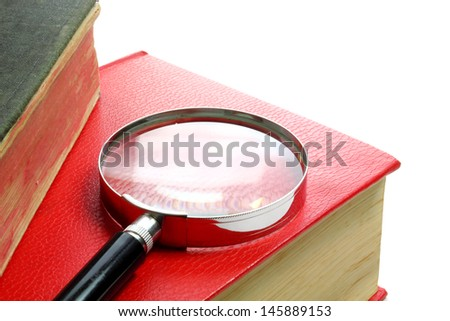 Magnification glass and books background - stock photo