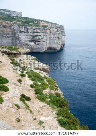 Magnificent Ancient Cliffs on Mediterranean Sea Covered in Lush Vegetation, Malta Island of Gozo, Xlendi Bay - stock photo