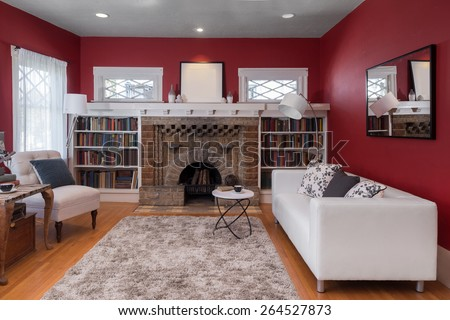 Magnificent decorated Living Room in Red with centered stone fire place, fitted bookshelves around, designer couch with pillows, natural colored fine sisal rug, wooden floor, chair, mirror and books. - stock photo
