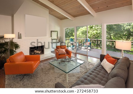 Magnificent living room interior in mid century home with view window, sliding doors and hardwood floor. Couch with hand-woven natural colored fine sisal rug open space living room within nature. - stock photo