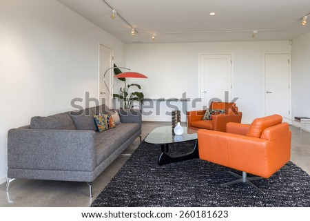 Magnificent living room interior with view build in drawers and polished concrete floor. Couch with round glass table and hand-woven natural colored fine sisal rug in open space living room. - stock photo