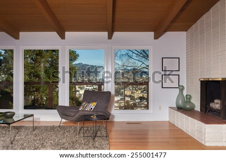 Magnificent living room interior with view window, french sliding doors and hardwood floor. Designer chair and natural colored fine sisal rug open space living room with fire place and dining area.  - stock photo