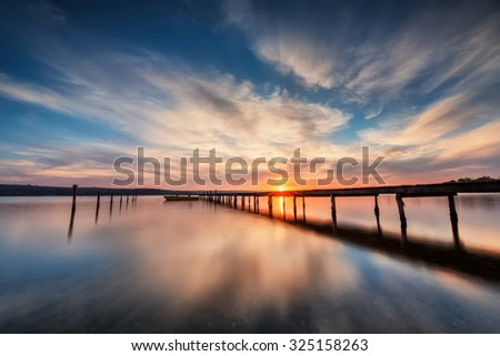 Magnificent long exposure lake sunset with boat and a wooden pier - stock photo