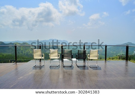 Magnificent outdoor terrace with chairs on sunny terrace with bay view and decoration in contemporary home. - stock photo