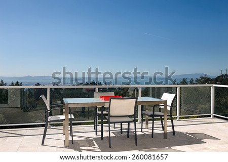 Magnificent outdoor terrace with chairs, table on sunny terrace with bay view and decoration in contemporary home. - stock photo