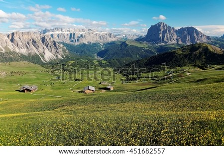 Magnificent panoramic view from Seceda with Sella and Sassolungo-Sassopiatto Mountains in background, farmhouses in the valley & green meadows filled with wild flowers in Col Raiser, Dolomites, Italy - stock photo
