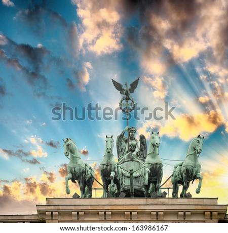 Magnificent Quadriga sculpture over Brandenburg Gate, Berlin. Sunset colors in winter. - stock photo