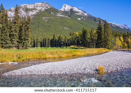 Magnificent valley in Banff National Park. Beneaped autumn stream with a pebbly bottom flows among the mountains and pine forests - stock photo