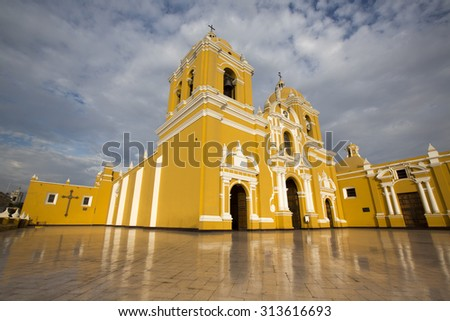 Magnificent yellow cathedral with a beautiful blue sky and light reflections in Trujillo, Peru - stock photo