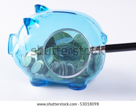 Magnified coins in a piggy bank. Studio shot. - stock photo